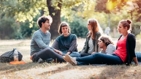 Studierende sitzen in der Herbstsonne auf einer Wiese.