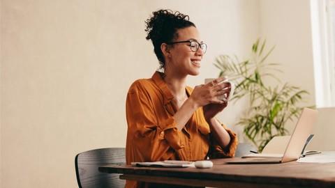 Eine Frau sitzt mit einer Kaffeetasse vor der Hand vor ihrem Laptop und nimmt an einem Onlinemeeting teil.