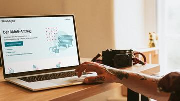 Junger tätowierter Mann sitzt am Laptop und bearbeitet seinen digitalen Bafög-Antrag.